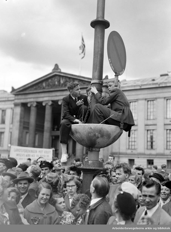 """17. mai 1953. """"Noen av russetogets tilskuere søkte tilflukt i en blomsterdekorasjon""""."""