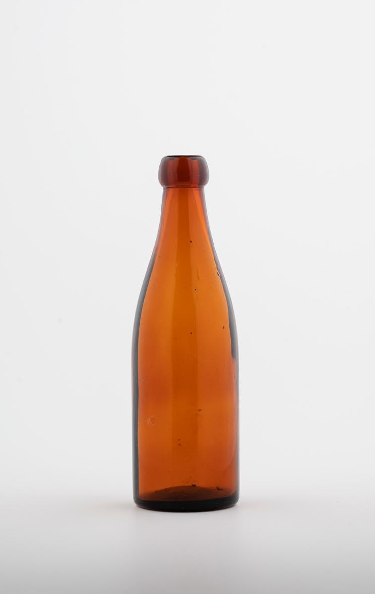 slank flaske i glass til omtrent 3-5 dl. Rund tut med ganske smal åpning.