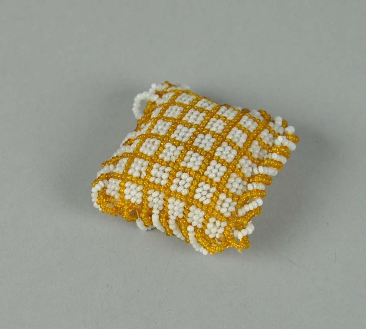 Liten lekepute. På framsiden har puten perlet rutedekor i gull- og hvitfarge. Baksiden av puten er trukket med silke.