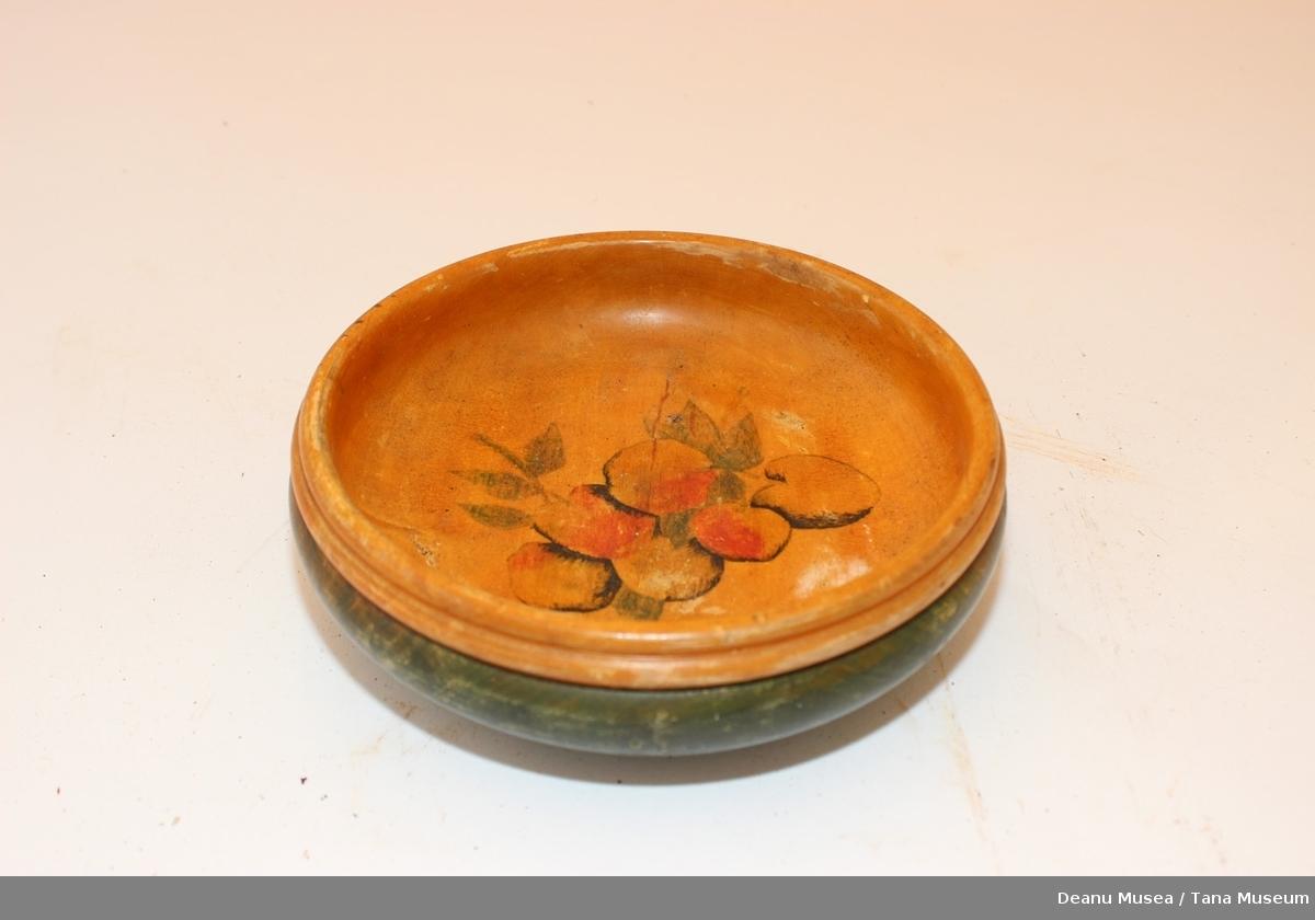 Rund skål av tre. Malt grønn på utsiden. Innsiden er bunnfargen oransje og i bunnen er det malt 6 epler e en klase.
