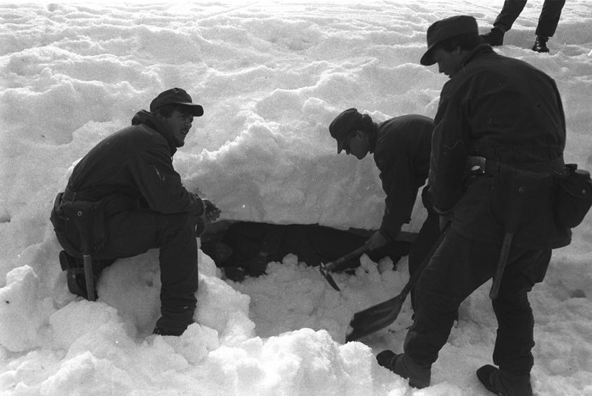 Tre befalsskoleelever graver frem en markør fra en snøskavel.