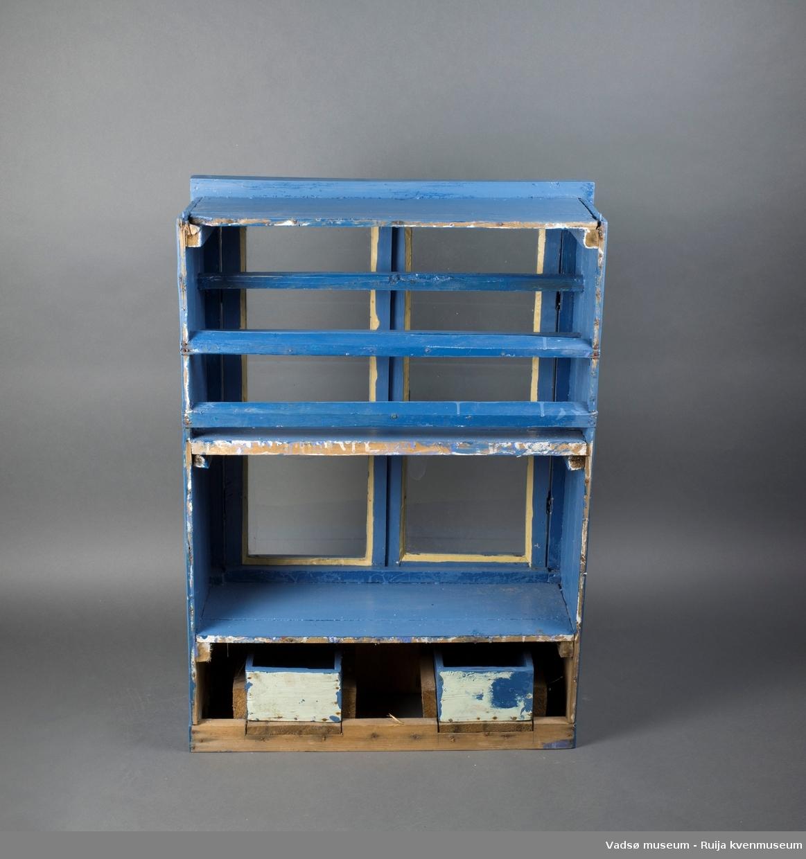 Overskap med glassinnfelte dører. To hyller, den øverste med horisontale spiler. Foran på skapet under dørene er to små rektangulære skuffer. Den ene skuffa mangler håndtaksknott. Skapdørene er hengslet og har skyvelås i metall.