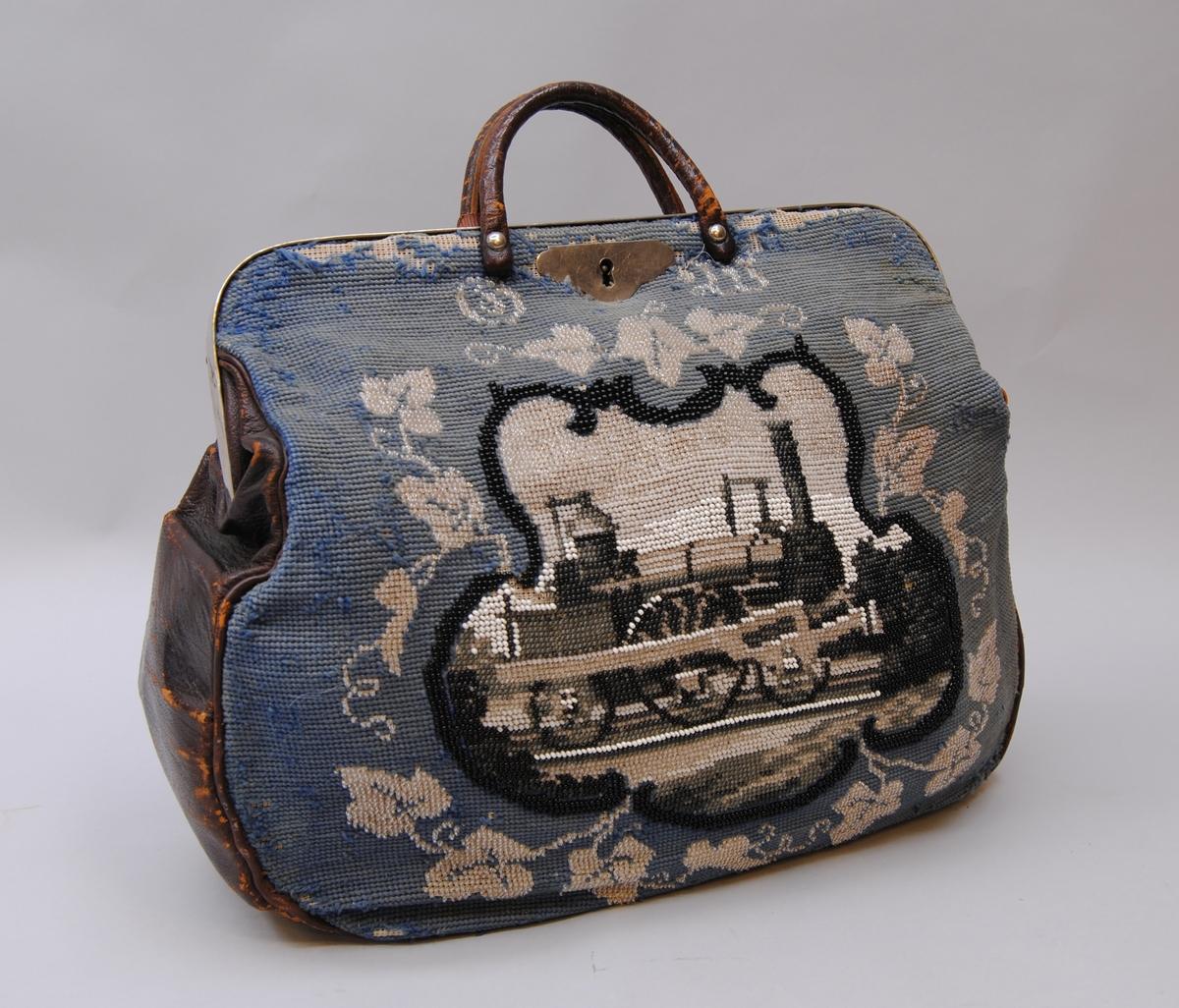 Väska med broderad framsida och svart baksida av skinn. Svarta skinnhandtag. Broderiet är utfört på stramalj med färgade glaspärlor och yllegarn. Motivet är ett ånglok i färgerna svart, grått och vitt på ett fält broderat med blågrått yllegarn. Väskan är skodd med förkromad metall, och har ett låsbleck framtill av samma metall.