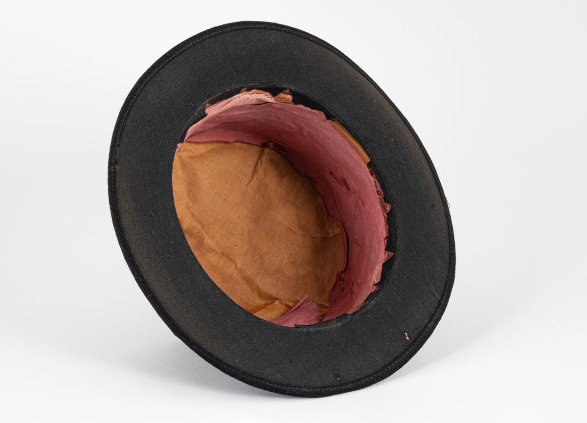 Svart flosshatt med myk pull og stiv brem. Pullen er foret med rød silkestoff. Det er pålimt en liten avlang bit av skumgummi på innsiden av pullen ved bremkanten.