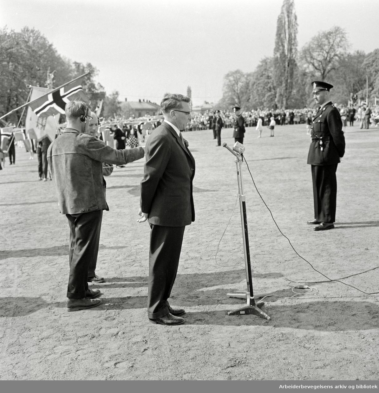 Formann i 17. mai-komitéen, Olav Brunvand, holder tale foran slottet. Haagen Ringnes fra NRK (med headset og mikrofon) til høyre. 17. mai 1960.