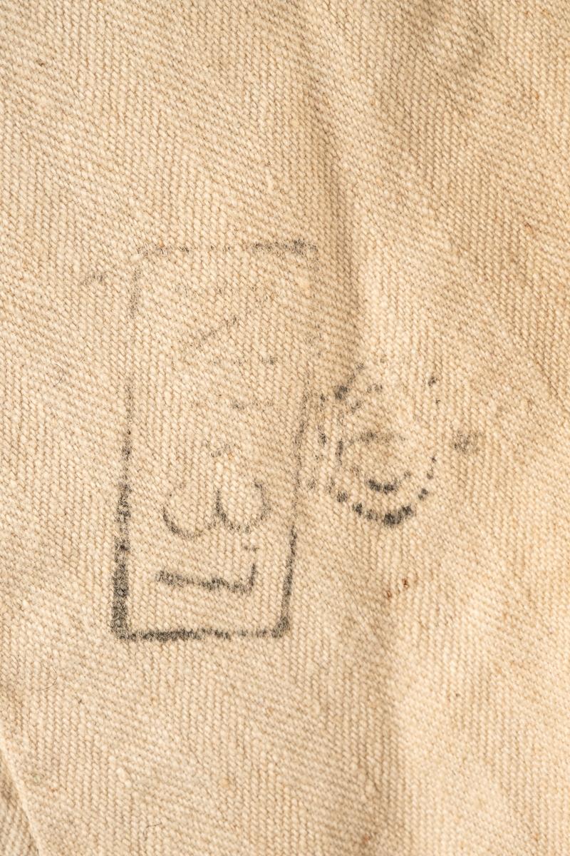 """Fangejakke, trolig fra en Gardeunirform. Jakken er mørk blå fôret i naturhvit lin på kroppen og lysegrå lin i ermene og kragen. Jakken har tilsammen 5 metallknapper og 4 hekteknapper. Det er 8 knappehull som tyder på at 3 knapper manlger.  På høyre bryst er påsydd et merke med fangenummer. På venstre erme er det påsydd et merke med et rødt kors og et avlangt merke med blå stripe i midten.  På innsiden av jakken er det to stempler. En i nakken """"Garden"""" og omtrent på midten av ryggen """"NI 37"""".  På skulderne er det små rester av rød stoff.  Ved kragen henger det en merkalapp med nr """"441""""."""