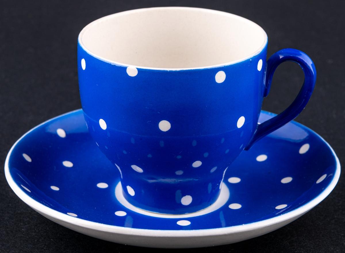 Kaffekopp med fat,modellAI i dekoren blå Amanita. Dekoren är i en blå glasyr med vita prickar.