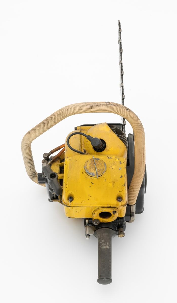 """Motorsag av typen Partner R11 beregnet for en person, enmannssag. Saga har påmontert sverd, sagkjede (skovltannkjede) og barkstøtte. Sverdet på denne saga er langt, 22"""" (cirka 55 cm). Saga ser for registrator ut til å være tilnærmet komplett, skrue til luftfilteret (luftinntaket) mangler. Sags komponenter er i hovedsak utført i stål, aluminium og presstøpte metallegeringer. Fremre og bakre håndtak er polstret med gummi. Saga har stående sylinder med eksospotte, lydpotte, (lyddemper) i front. Bensintanken er plassert rett bak sylinderen. Rett under tanken er sagas luftinntak (luftfilter). Forgasseren (membranforgasseren), gjenfinnes også rett under bensintanken. Chokehendel og gasshendel (også funksjon som clutch) er plassert rett bak forgasseren ved det bakre håndtaket, betjenes med tommelfinger. På venstre side av saga, utenpå starthuset, er oljepumpa plassert. Pumpa er forbundet med oljetanken på undersiden av sagkroppen. Påfylling av kjedeolje skjer  på høyre side nede på sagkroppen. Sagas totaktsmotor krever oljeblandet bensin i blandingsforholdet 1:20.  I bakkant, på undersiden av sagkroppen, er det påmontert en gummipute som gir saga støtte når den settes på bakken eller et annet underlag.   Ut fra medfølgende påskrevet lapp til saga og andre kilder, har den disse tekniske spesifikasjonene: Motor: Totaktsmotor Sylindervolum: 90 kubikkcentimeter. Ytelse: Yter 5 hestekrefter ved 6000 omdreininger per minutt. Vekt: 9,3 kg (10,9 kg med 15"""" sverd og fulle tanker)  Drivstofftank: 0,9 liter. Oljetank: 0,5 liter.  For en teknisk beskrivelse av saga se vedlagt fil under fanen """"Referanser til filer""""."""