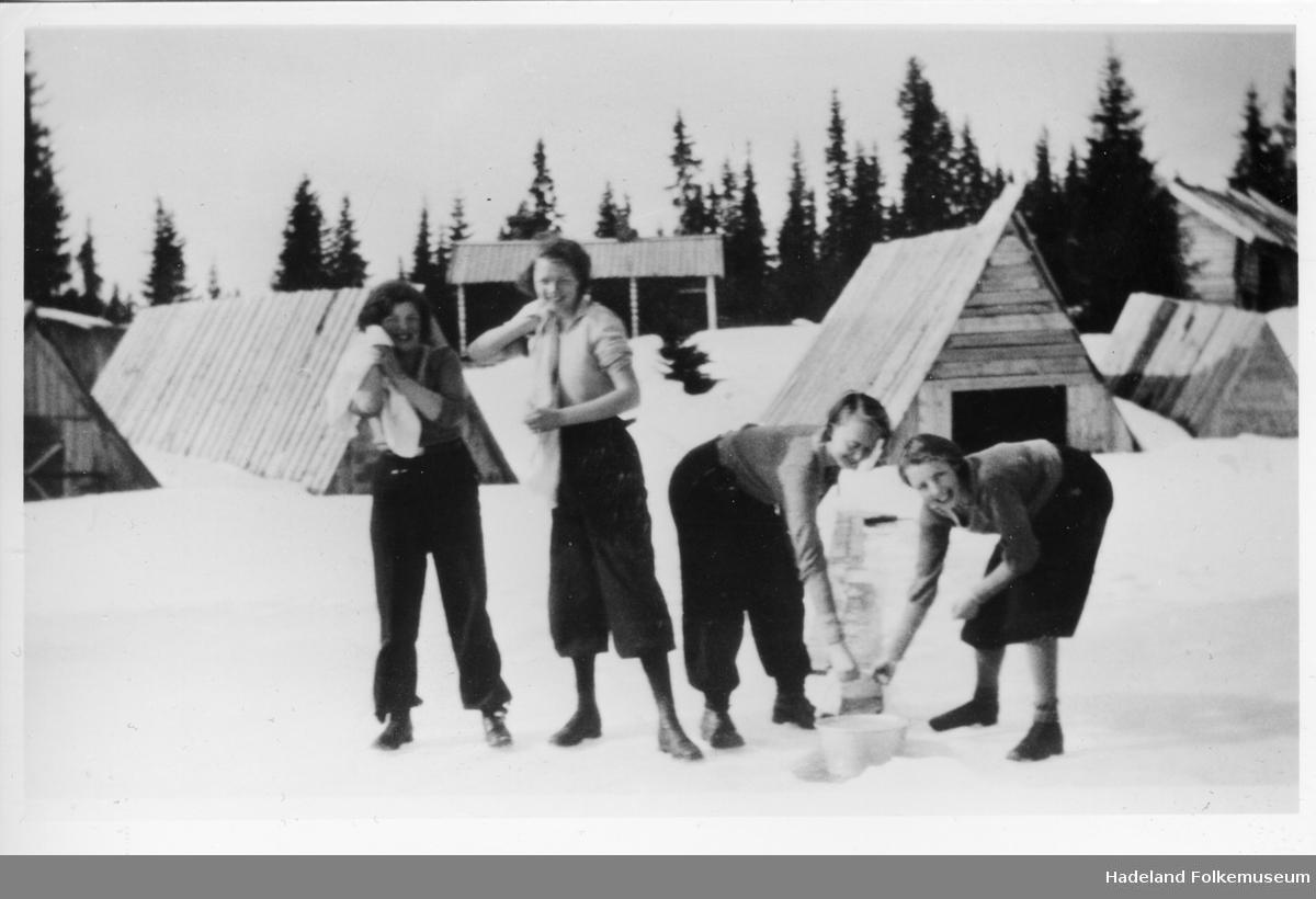 Fire jenter står på isen og vasker seg på Vassbråa. Båthus og hytter i bakgrunnen.