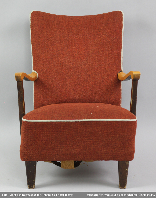 Lenestolen tilhører en sofa i samme stil. Den er polstret i rygg og sete. Den er trukket med rødt stoff og har naturfarget kantbånd som rammer inn hele møbelet. Armlenene er festet i ryggen og i ramma. Treverket på begge møblene er mørkbeiset og lakkert. Oversidene av armlenene til stolen er derimot trefarget og er overtrukket med transparent lakk. Benene er firkantede. Ramma har festet striper av strie med spiker på undersiden. I striene er det festet sylinderfjærer som på oversiden er festet med hyssing til hverandre. På fjærene ligger et lag med striestoff og oppå der igjen er det et fyllmateriale. Øverst kommer trekkstoffet som er festet på undersiden av ramma.