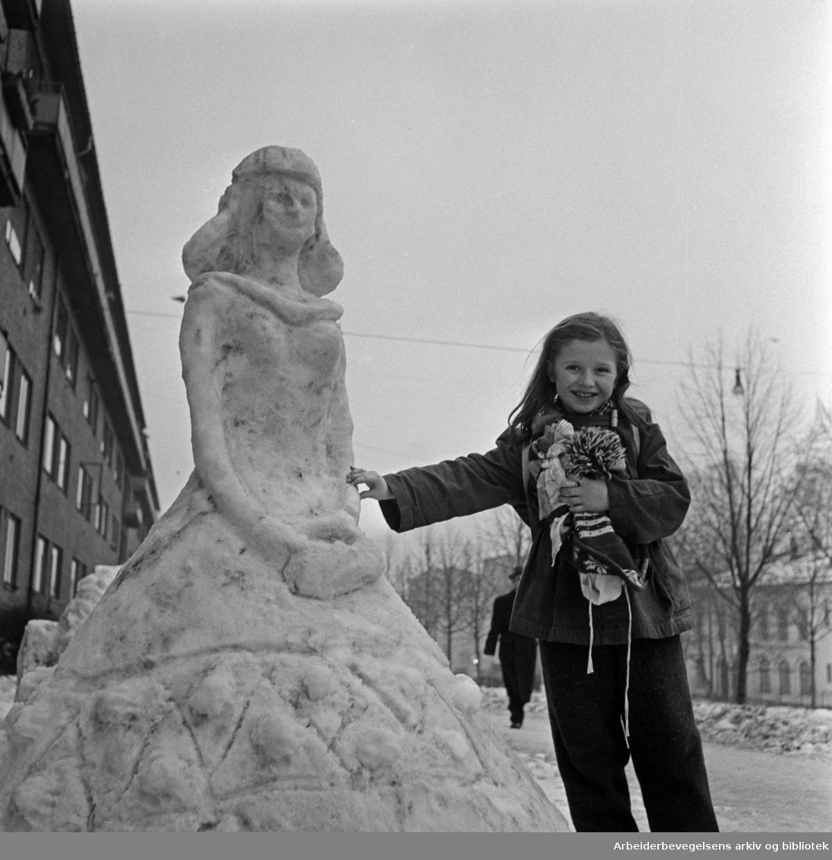"""""""På hjørnet av Ole Bulls gate og Chr. Michelsens gate har noen laget denne flotte snøskulpturen. Den vekker daglig stor beundring hos forbipasserende. På bildet ser vi Lise Gun Wagle ved siden av kunstverket. """" Vinteren 1958."""