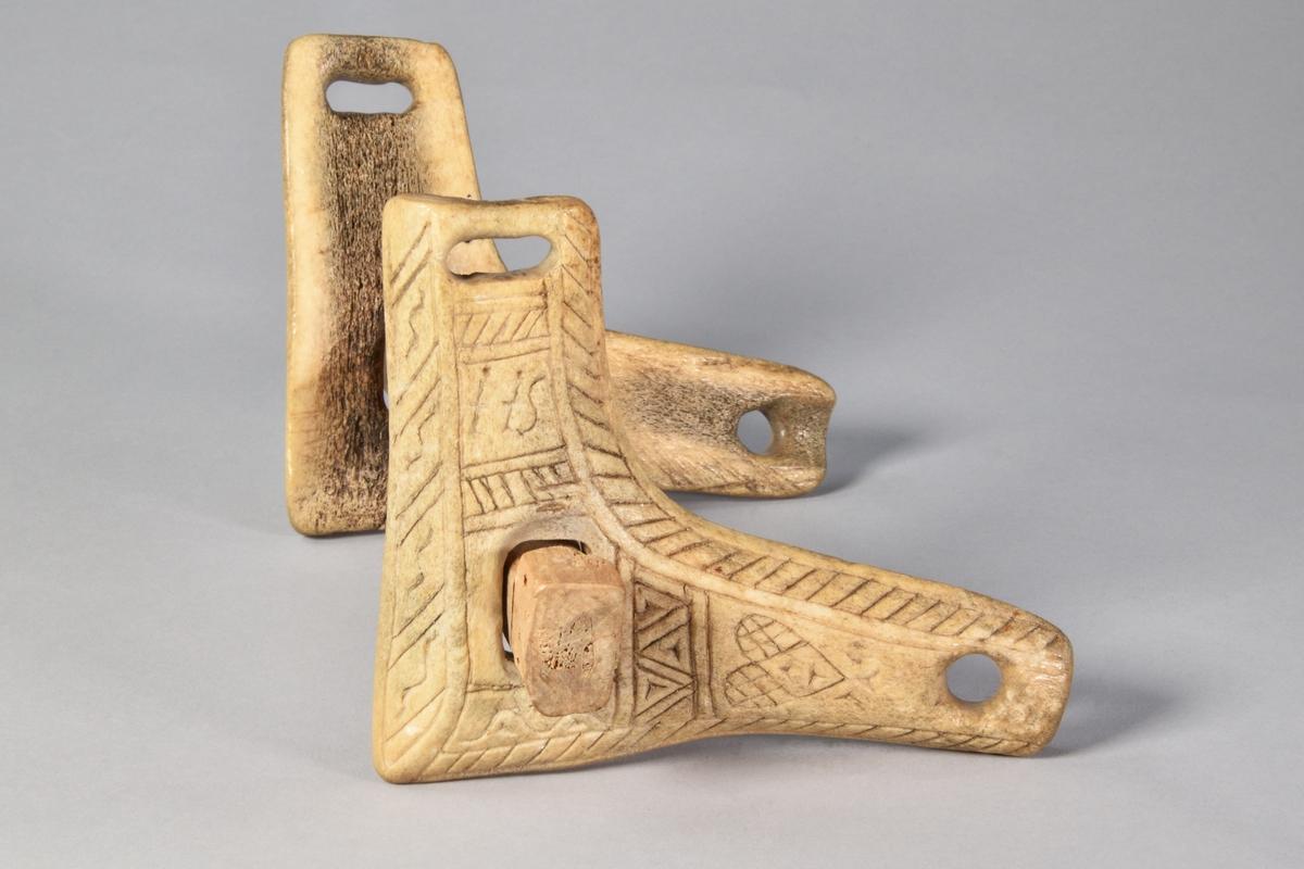 Munbett av trä, rakt, med två vinklade rörliga sidostycke av horn. Rik ornamentik på sidostyckena.