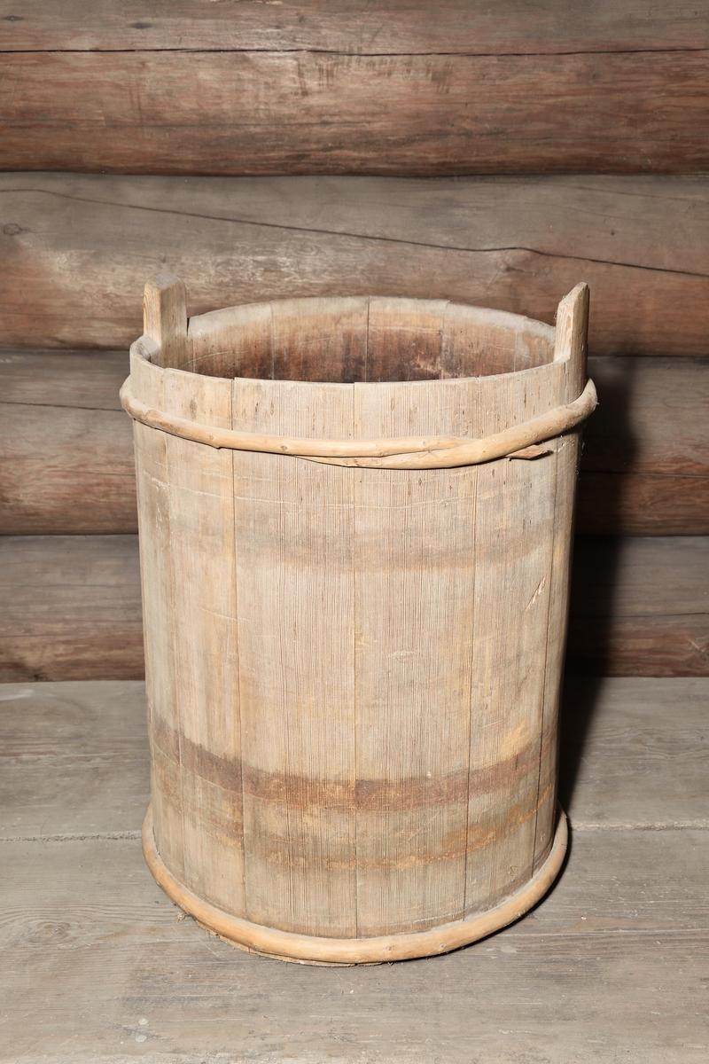 Mjölkså av furu, cylindrisk, laggad: 14 laggstavar och 2 träband - ursprungligen även ett järnband. 2 laggstavar förlängda till handtag. Raka sidor.