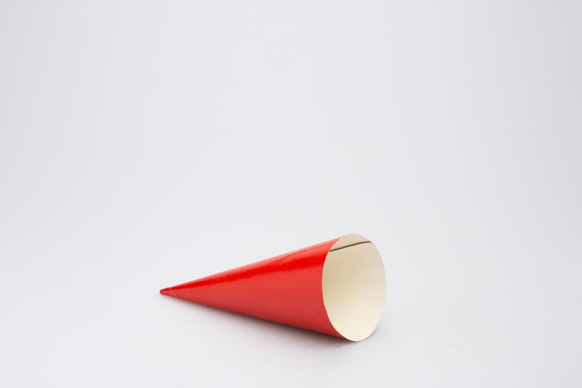 Kjegleformet iskrempapir (kremmerhus) i aluminium og papir. Kremmerhuset er matt i rødt med hvit tekst på utsiden, og uten farge (hvit) på innsiden. Deler av teksten er ikke synlig. Det er forskjellig på hvert kremmerhus hvor mye av teksten som er synlig.