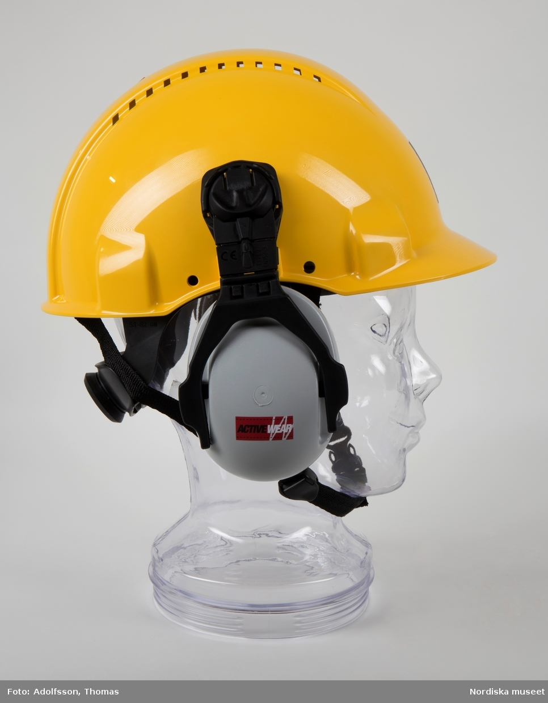 """Gul skyddshjälm 3M för industrin, storlek 53-62. Framställd för att skydda bäraren mot föremål som kan träffa huvudet. Hjälminredet består av svarta remmar, svettband och nackband som kan justeras till önskad passform. På hjälmen sitter två grå hörselkåpor """"Active Wear"""" som ska fällas ned för skydd i bullriga miljöer. Vid arbetsläge fälls kåporna ned och trycks in mot öronen, så att de sluter tätt om dessa. Vid viloläge trycks kåporna utåt och vid parkeringsläge upp till nästa fasta läge. När hjälmen inte är i bruk ska hörselskydden vara nerfällda och intryckta (enligt bruksanvisningar som medföljer produkten). På framsidan av hjälmen finns en fastklistrad etikett med """"B-safe""""-logga. Enligt givaren är det """"ett avtal som anställd ingår som säger att du ska arbeta på ett säkert sätt, med säkerheten i fokus."""" /Karin Dern 2019-09-06"""