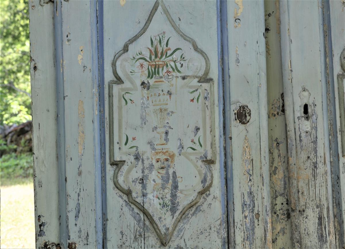 Skap med to låsbare dører. Malt i lyseblå, grålig farge og begge dørbladene dekorert.  men malinga er defekt.