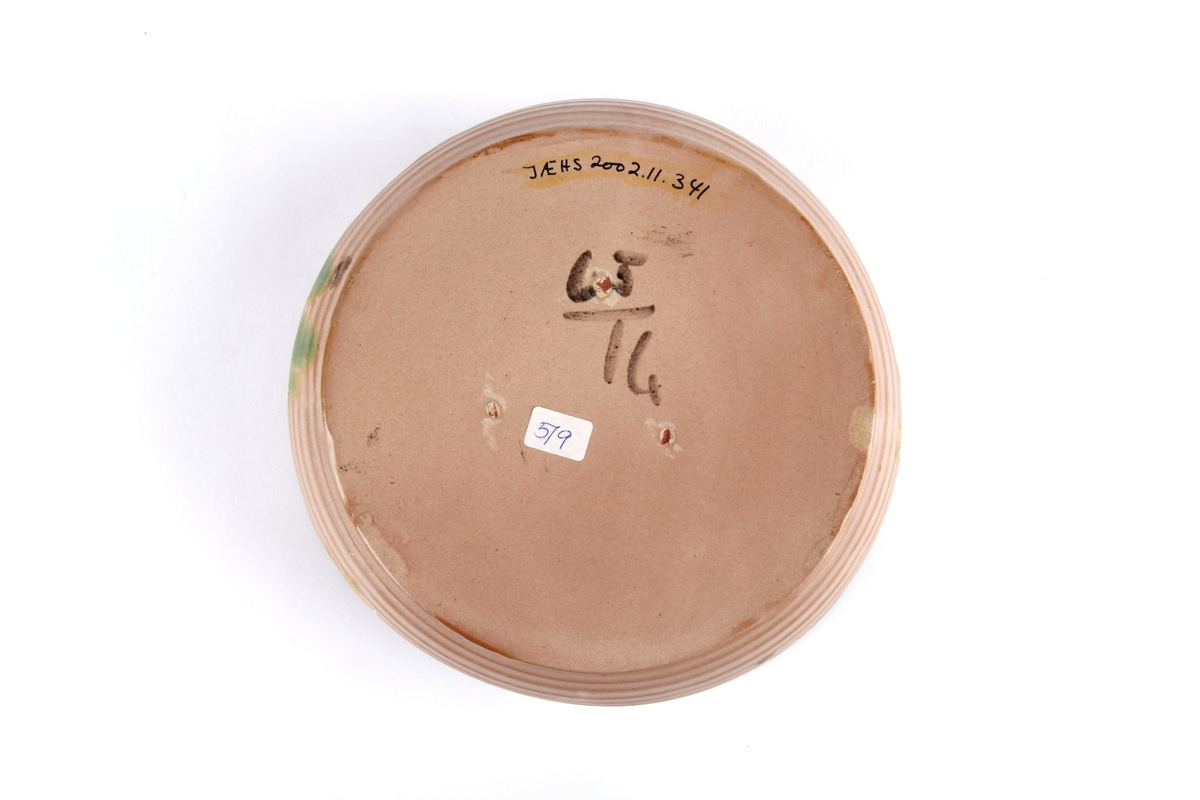 Glasert keramikkskål med utvendige riller og bølget kant.
