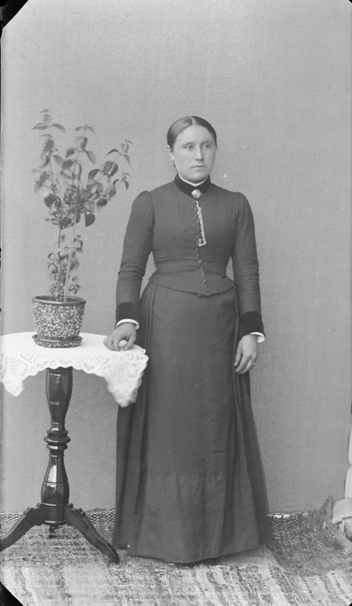Kvinne som står ved siden av et rundt bord med heklet duk og blomster. Hun har glatt hår med midtskill, kledd i lang stakk og overdel med mansjetter i mørkt stoff