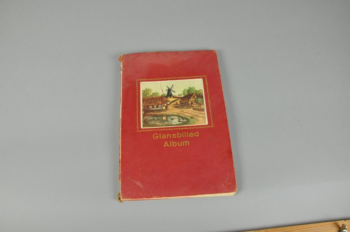Glansbildealbum med rødt omslag av papp. Bindingen har løsnet.