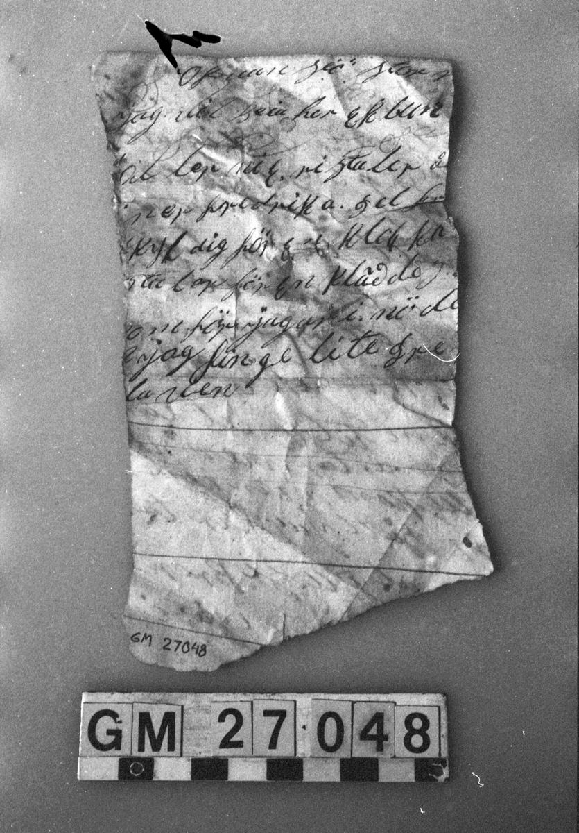 Papper. Del av pappersark. Lumppapper. Skrivet med sepiabläck. Text på bägge sidor. Ena sidan: Ur brev från 4 mars 1858. Andra sidan: Ofvansjö Storvik osv.