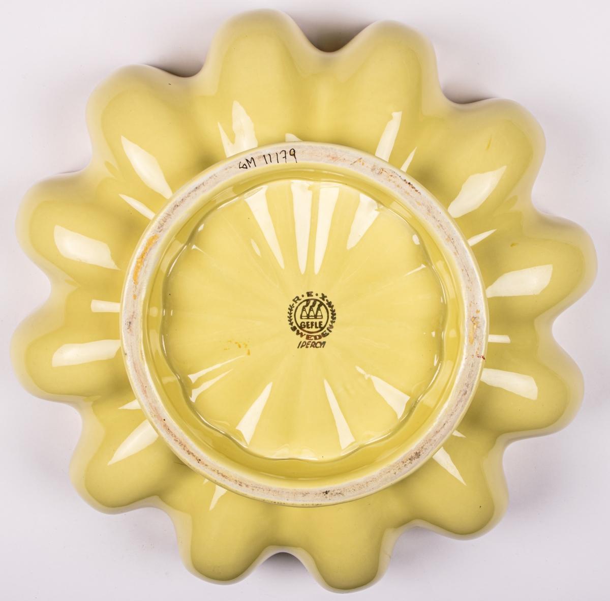 Skål av flintgods med veckad kant, gul glasyr med dekor i guld.
