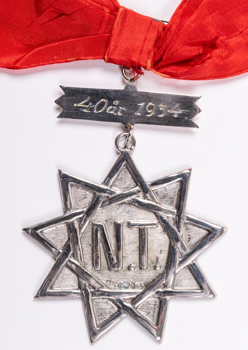 """Stjärna av silver ihängande banderoll, fastsydd i rött band med rosett. Stjärnan 9-uddig. I stjärnans mitt läses """"N.T."""".  Under bokstäverna stämplar: AUW, G, H8 Stjärnan: 5,7 cm höjd, inklusive ögla. På banderollen av silver läses på framsidan: 40 år 1934. På baksidan: 22/12 1894. Regalien fästes med svart säkerhetsnål."""