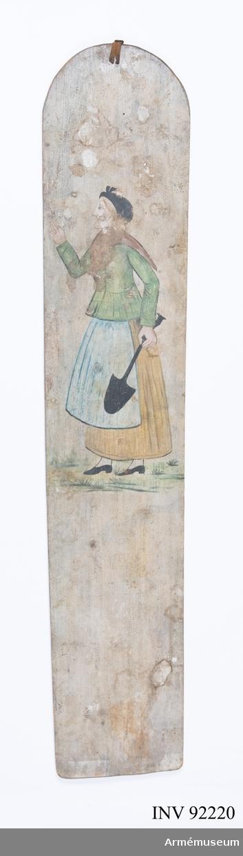 Träskylt bemålad på båda sidor. På ena sidan en soldat i uniform m/1845 för Andra Livgrendadjärregementet. Han bär troligtvis käppi samt livrem m/1864. På andra sidan en kvinna klädd i grön jacka, gul kjol och blått förkläde. På huvudet har hon svart klut och över axlarna en brun sjal. I handen håller hon en spade.