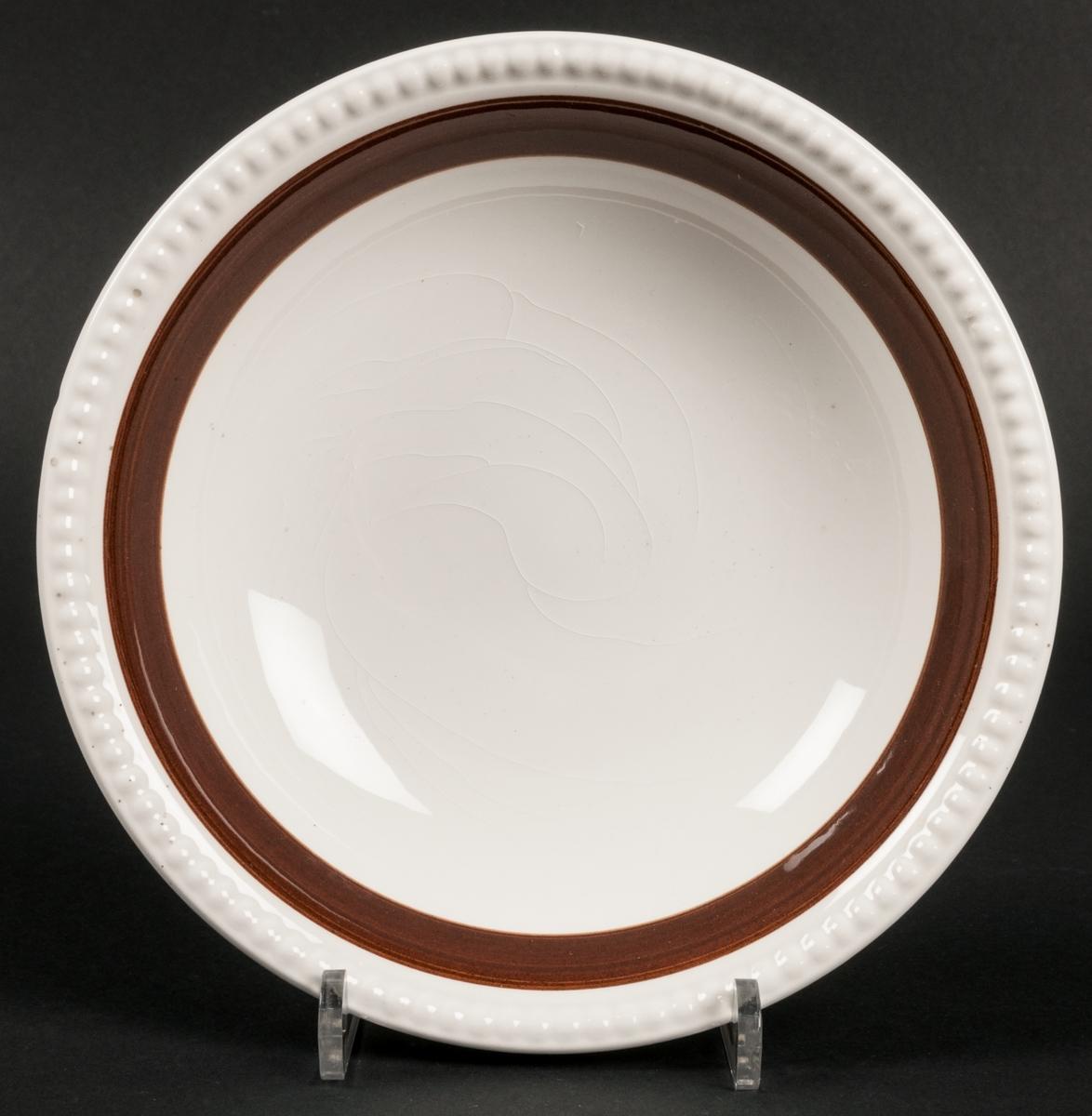 Djup tallrik, dekor Malta. BDR.  Dekorerat med brunt enkelt band och pärlstav i godset. VDN-märkt F555.