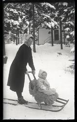 Kvinna med barn på sparkstötting