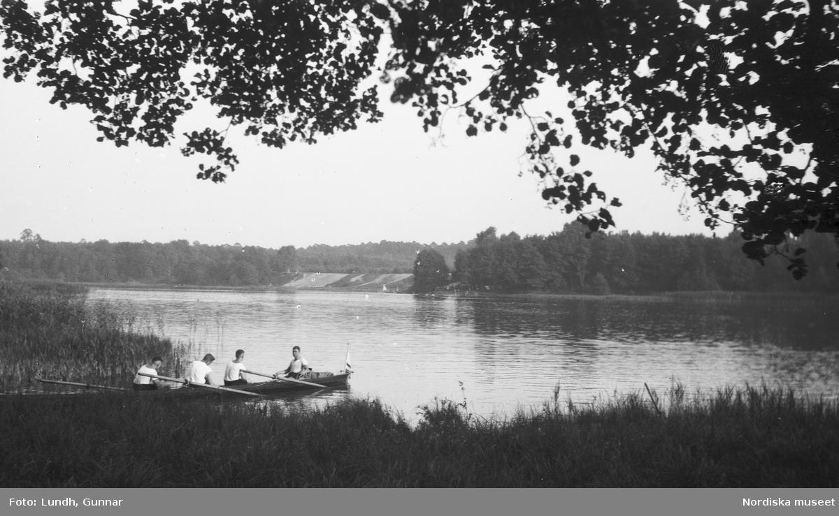 Motiv: Utlandet, Berlins Omgivningar 157 - 177 ; Exteriör av en väderkvarn, landskapsvy med en sjö och skog - fyra män sitter i en kanot, en man och en kvinna sitter i en båt och matar en svan.