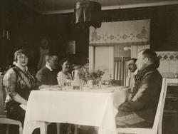 Ett sällskap samlat kring matbordet.