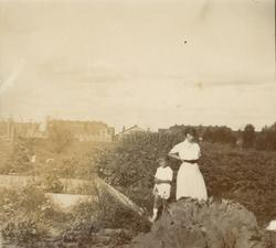 Kvinna med barn på trädgårdsland.