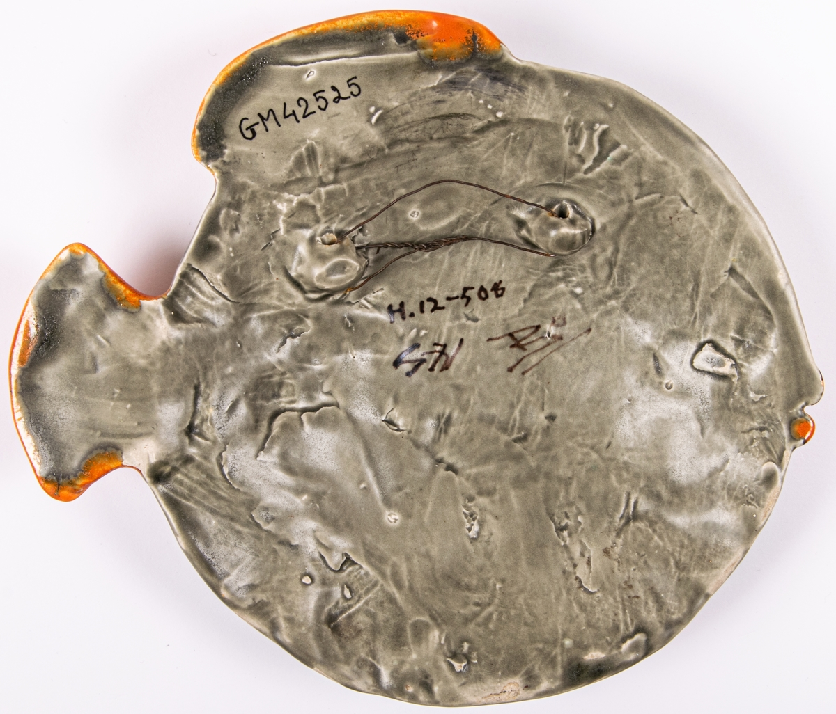 Väggfigurin i keramik i form av en fisk.