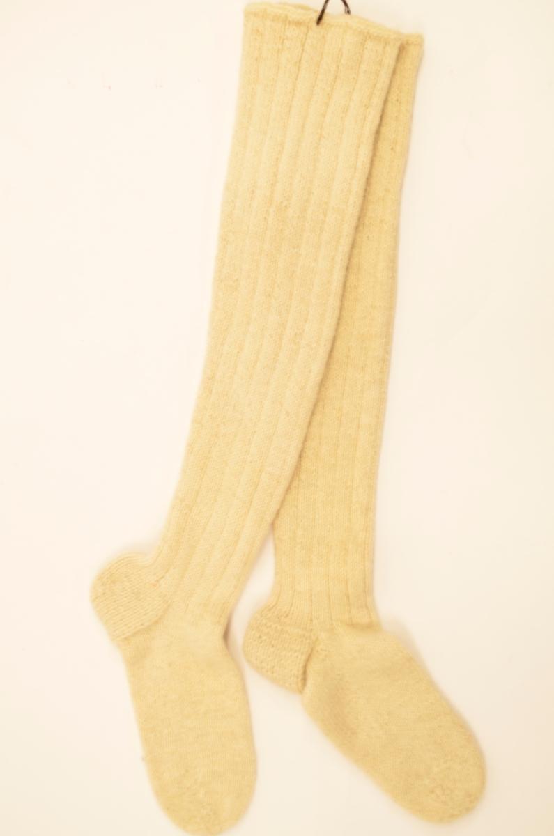 Strømper, a+b, lang, handstrikka i kvitt ullgarn, 4 rett og 1 vrang. Hælen er strikka med dobbelt garn. Ikkje brukt ?