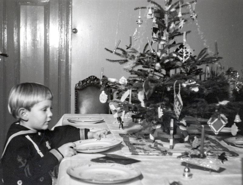 Svart-hvitt foto av en liten gutt i matrosdress som dekker bordet. På bordet står også et lite juletre. (Foto/Photo)