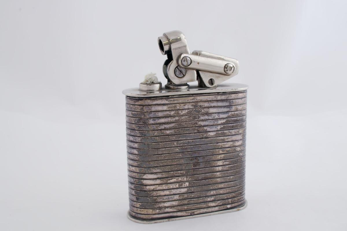 Rektangulær bordlighter. Bensinbeholderen sitter i lighterens nedre del og kan trekkes ut. Fra bensinbeholderen fører en veke opp til vekeholderen. Selve kroppsstykket er av sølv og har 20 langsgående riller.