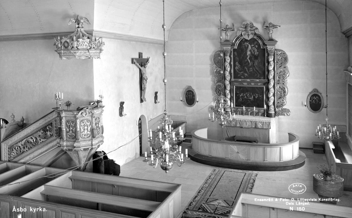 Interiör av Åsbo kyrka. Den vackra predikstolen i barockstil är skänkt till kyrkan av Gabriel Ribbing och hans hustru Beata Sparre. Hon skänkte också en kopia av hovmålaren Georg Schröders nattvardsbild i Drottningholms slottskyrka. Målningen hänger som en av kyrkans två altartavlor vid den dominerande altaruppsatsen, även den i barockstil. Den andra altartavlan är ett ateljéarbete från 1600-talet som skildrar Jesus nedtagande från korset. Dopfunten från 1200-talet är kyrkans äldsta inventarium.