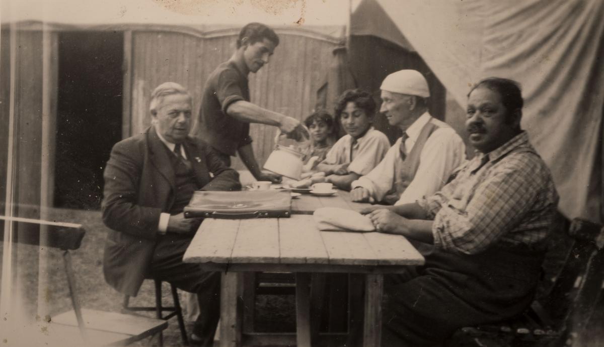 Bilden är tagen i Falun, augusti 1950. I anteckning till bilden står att det är sonen i familjen som serverar kaffe till en magister Jaiko, finsklärare, och redaktör Sandberg. Senare blev det avslutning på skolan. I bakgrunden syns en vagn och tältdukar.