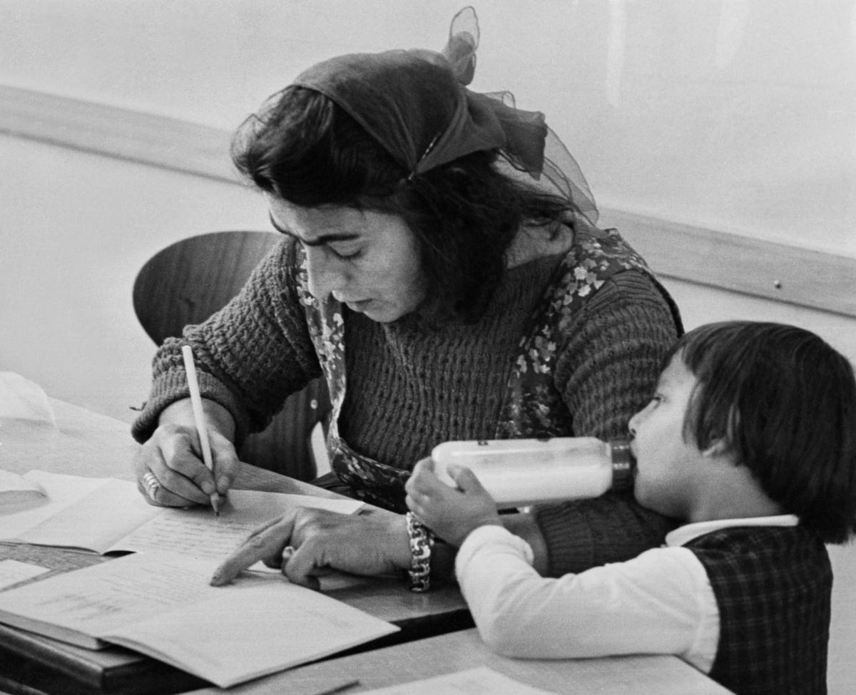 """En kvinna sitter vid ett bord och skriver i en skrivbok. Texten till bilden uppger att kvinnan fick börja i grundskolans första klass ett år tidigare. Hon har redan hunnit läsa in tre årskurser. Bredvid kvinnan sitter hennes treåriga dotter, som på grund av svårigheten att få tag på barnvakt får komma med sin mamma till skolan. Trots att Sverige haft skolplikt sedan 1842 har inte alla barn haft rätt att gå i skolan. Redan 1933 skrev Johan Dimitri Taikon till skolöverstyrelsen och bad om skolundervisning för romska barn. Först tio år senare blev han hörsammad, då han tillsammans med den frikyrkligt engagerade Otto Sundberg blev beviljad 1500 kronor för att starta en """"försöksskola"""". Denna verksamhet kom senare att drivas för Stiftelsen Svensk Zigenarmission, grundad 1945, som drev sommarskola för romska elever under hela 1940- och 1950-talen. Eleverna var mellan 6 och 60 år och satsningen blev mycket medialt uppmärksammad. Först efter att alla romer fick bli bofasta på sextiotalet, fick samtliga romska barn möjlighet att gå i skola året om. Efter omfattande opinionsarbete och ideellt engagemang startades den första vuxenutbildningen 1964."""