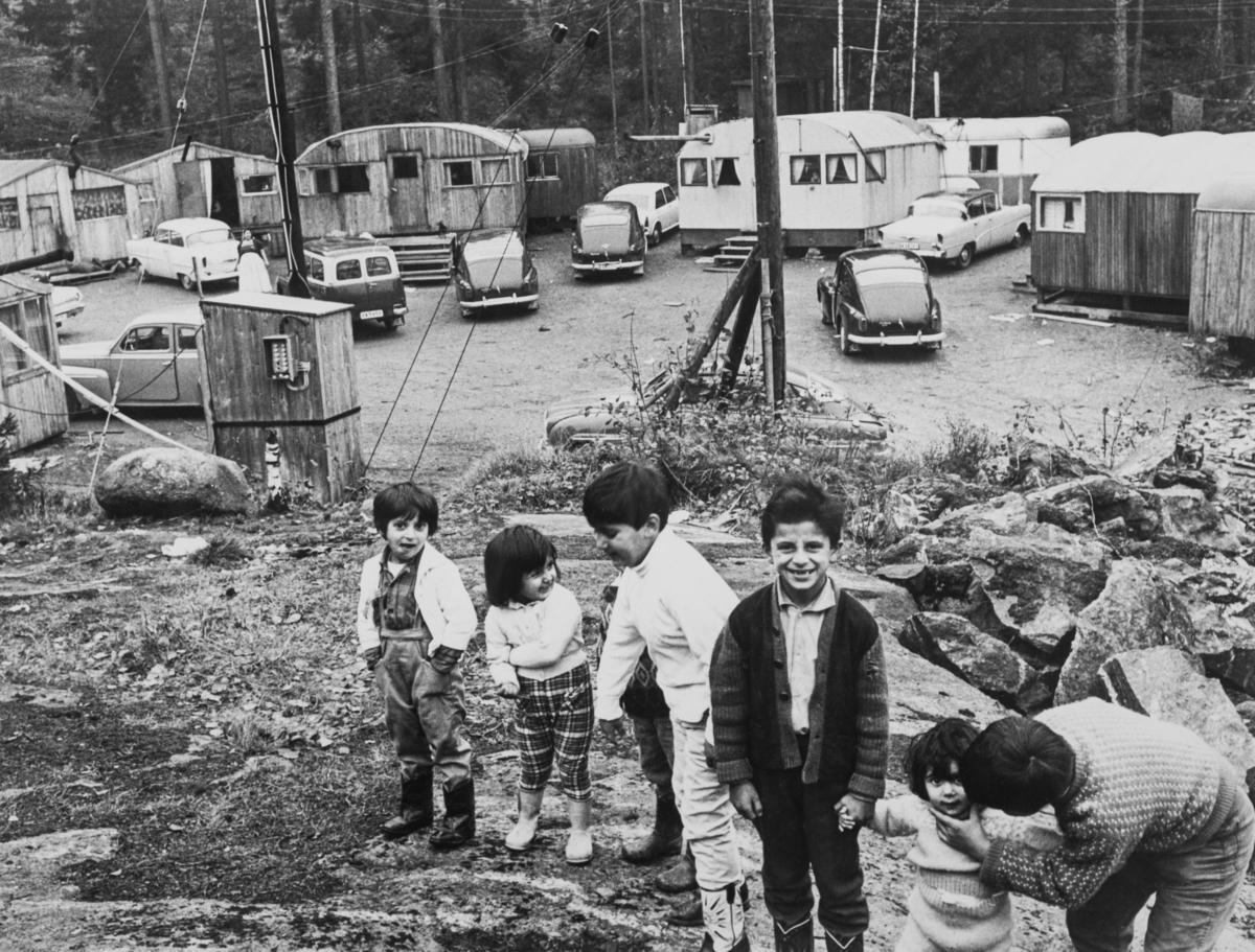 """En samling barn står uppställda för fotografering i ett av de läger som Stockholm stad upprättade för romer i slutet av 1950-talet. Efter att de svenska romerna i Sverige erkändes som medborgare år 1952 hade debatt uppstått debatt kring gruppens svåra levnadsförhållanden. En statlig utredning genomfördes under 1954-1956 där en av slutsatserna blev att fast bostad var nyckeln till att lyckas med skolgång och arbetsliv. Efter att även Stockholm stad genomfört en utredning (1955-57) upprättades två lägerplatser vid Flaten, samt en försöksverksamhet med provisoriska bostäder i Hammarbytäppan. Tanken var att romerna skulle bo här tills dess att bostadsfrågan löstes. De två lägerplatserna vid Skarpnäck låg med omkring 2 kilometers mellanrum. De kom att benämnas Ekstubben respektive Skarpnäckslägret. Skarpnäckslägret stod färdigt för inflytt i oktober 1959 och Ekstubben stod färdig för inflyttning 15 mars 1960. Lägren skulle finnas under en övergångsperiod innan fasta bostäder ordnats, men i realiteten drog bostadsfrågan ut på tiden och lägren blev kvar i fem år. I reportaget """"Vagabond eller vanlig människa?"""" av Roland Hjelte och Karl Axel Sjöblom som sändes i SVT i mars 1963 skildras livet i dessa läger under vintern 1963. I intervjuerna med de boende i lägret framhålls det akuta önskemålet om fast bostad. I lägret bodde det året 15-20 familjer och reportern berättar att människor har bott här flera år i väntan på att Stockholms stad ska lösa bostadsproblemet. Det är vinter, snön har fallit och vissa nätter gick temperaturen under nollstrecket inne i husvagnarna. En man berättar att han är uppe hela nätterna för att elda i kaminen. Han säger till reportern: """"När alla andra fått bekvämligheter ska vi också ha det. Vi kan inte ha det så här!"""". Det skulle dröja till maj 1964 innan de sista av de svenska romerna flyttade från Ekstubben. Senare användes Ekstubben dock fortsatt som lägerplats för romer som kommit till Sverige från andra delar av Europa. Bilden publicerades i sa"""