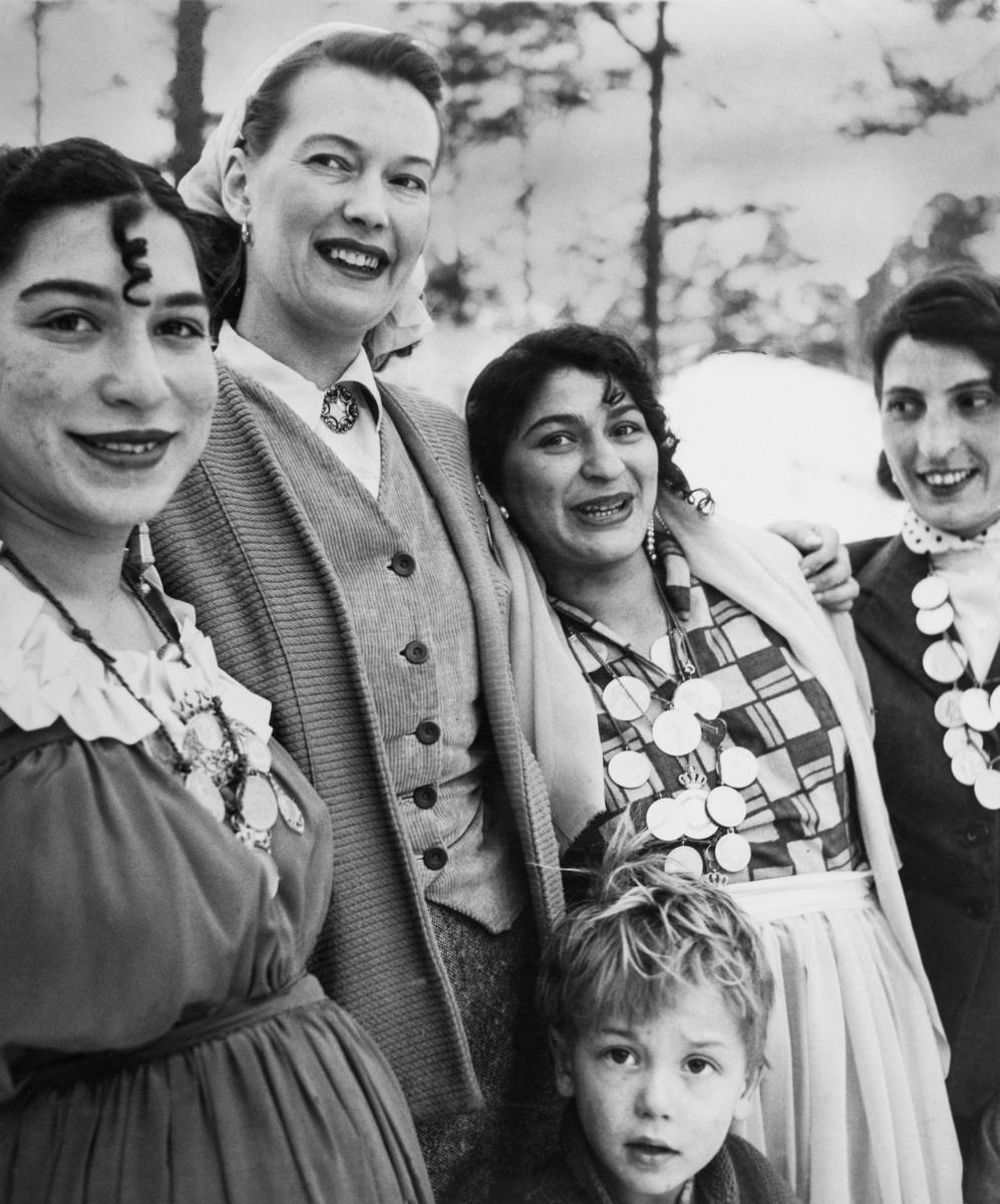 En grupp romska kvinnor ler mot kameran. Tre av kvinnorna bär mynt i kedjor runt halsen. Mynten är smycken såväl som ett sätt att bära med sig familjens kapital då man tvingas flytta, ofta med kort varsel med lite tid för packning. Toleransen för romer varierade mycket mellan olika samhällen, men romers närvaro har sällan setts som något positivt. Ofta fick man slå sig ned i samhällets utkant, man har förvägrats fast bostad och fördrivits. Efter att de svenska romerna i Sverige erkändes som medborgare år 1952 uppstod debatt kring gruppens svåra levnadsförhållanden. En statlig utredning genomfördes under 1954-1956 där en av slutsatserna blev att fast bostad var nyckeln till att lyckas med skolgång och arbetsliv. Från och med mars 1960 hade möjlighet att rekvirera statsbidrag för kostnader i samband med romers bosättning, vilket förenklade möjligheten för svenska romer att få tillgång till permantenta bostäder samt i förlängningen studier och arbete.