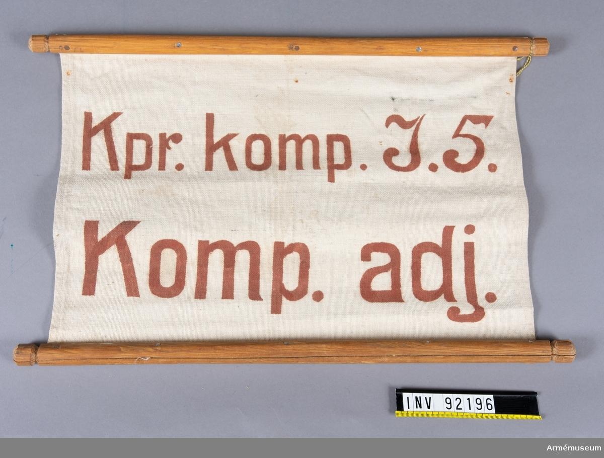 """Skylt av tyg av smärtingtyp fästa i träpinnar på långsidorna. Röd text: """"Kpr. komp. I.5. Komp. adj"""""""