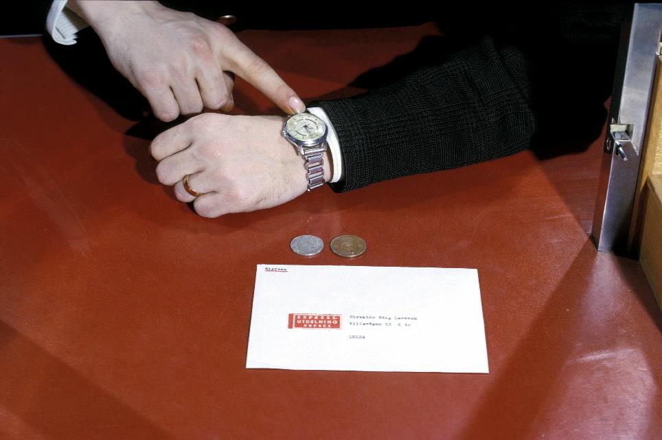 Seriebild H 3. Ett expressbrev lämnas in i kassa på potkontoret Stockholm 40. Det adresserade kuvertet är försett med expressetikett. Kunden visar med fing-ret på armbandsuret och antyder därmed att det är brådskande.