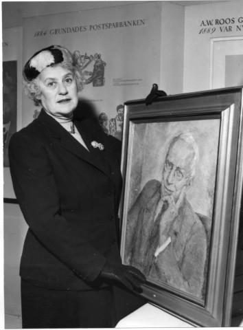 Konstnären Olga Raphael Linden-Hallencreutz med det av henne målade porträttet av museets grundare, postdirektör Erik Gustaf Lannge. Porträttet gavs till muséet av Föreningen Postmusei Vänner.