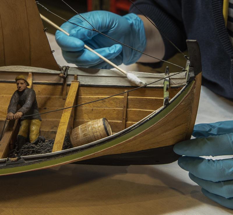 Konservator renser modellbåt med bomullspinne