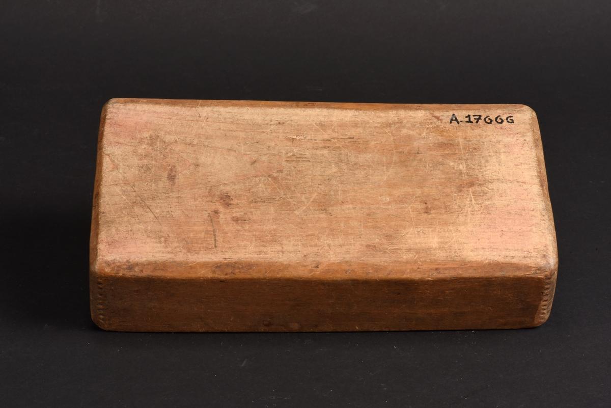 Kryddlåda av trä och skjutlock. Lådans yttre är skuren i ett stycke och har en inredning med sex fack. Skjutlocket har geometriska mönster i form av trianglar samt årtalet 1771 och initialerna MAD inskuret.