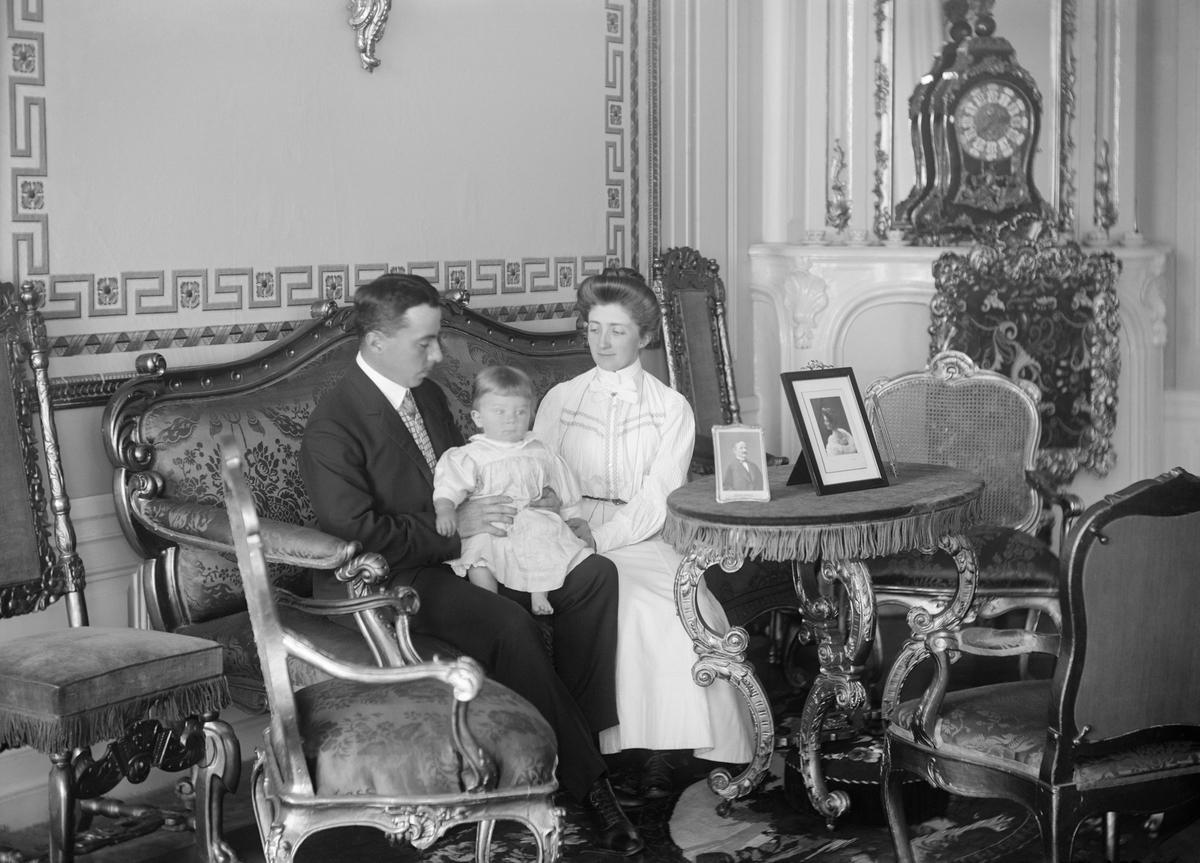 I salongen på godset Thorönsborg i Sankt Anna socken sitter Philip Bonde med sin son Carl Philip Bonde i knäet med sin hustru Anna Bonde, född Mörner intill sig.