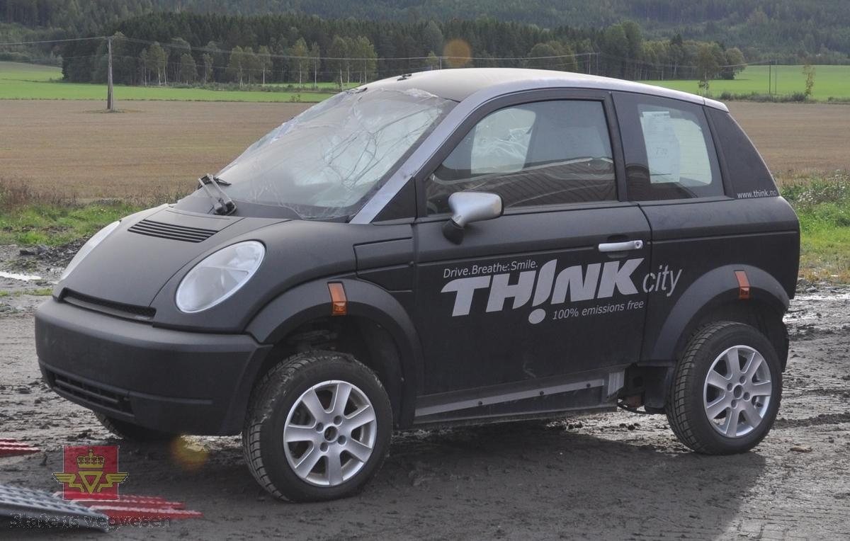 Sort sidekollidert elektrisk drevet personbil Pivco City/306/Piv5. Bilen er kollidert fra høyre side.   Bilen har et karosseri av termoplast, (polyetylen) og et tak av ABS plast. Underramme av stål og overramme av aluminium. Kollisjonsbjelker i dørene. Deformasjonssoner. Farget glass, sort og grått interiør. Den har en motor på 34 kW maks effekt, og et zebrabatteri som ved en temperatur over 200 grader inneholder 25 kWh energi.