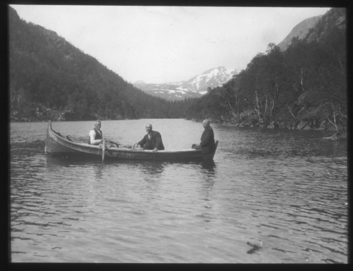 """N.592.a) Toven-vannet. N.4"" står det på glassplaten. Landskapsbilde med tre personer i en robåt på vannet.  Toven ligger i Vefsn kommune i Nordland."