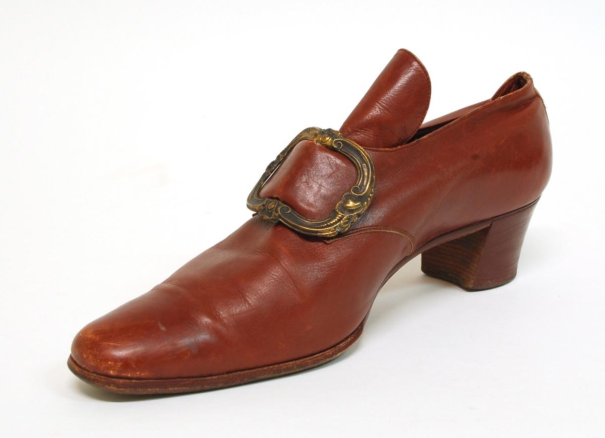 Ett par damskor av brunt läder med plös. Snörad, i fyra par snörhål, med resårband som döljs under ett skospänne av metall och läder. Limmad lädersula och skiktlimmad klack.